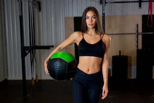 Mulher morena atraente em roupas esportivas em pé na academia segurando uma bola na mão