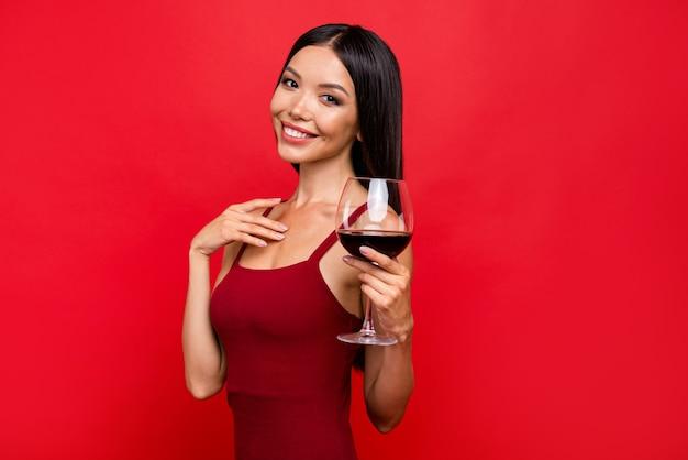 Mulher morena atraente em um vestido vermelho posando contra a parede vermelha