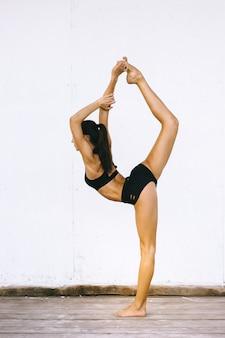 Mulher morena atraente fazendo exercícios de ioga de biquíni em um fundo branco