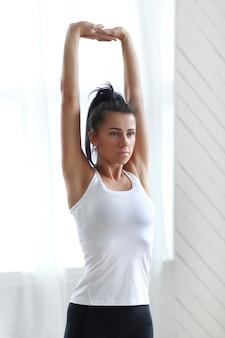 Mulher morena atraente fazendo ioga em casa.