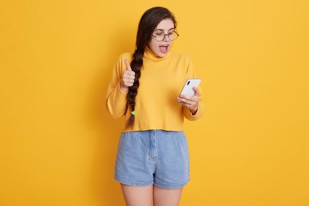 Mulher morena atraente, gritando algo alegremente enquanto olha para o telefone inteligente nas mãos dela