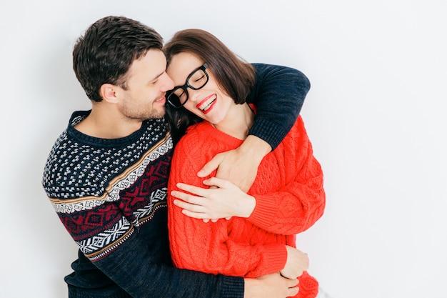 Mulher morena atraente jovem desfruta de tempo livre com o namorado, fecha os olhos e sorri alegremente