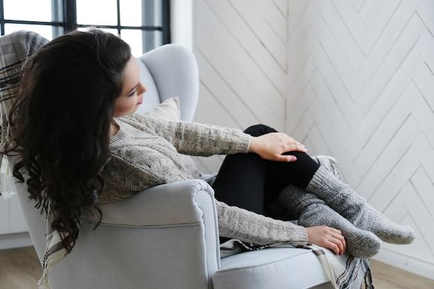 Mulher morena atraente posando no sofá