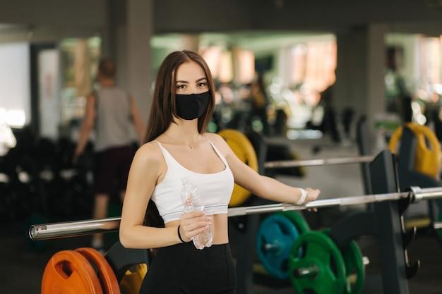 Mulher morena atraente tem uma pausa no ginásio. mulher com máscara protetora e segurar a garrafa de água.