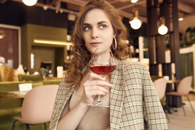 Mulher morena bonita elegante com copo de vinho tinto