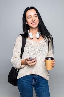 Mulher morena bonita jovem atraente enquanto estiver usando telefone inteligente e bebendo café isolado na parede cinza