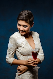Mulher morena bonita no vestido de noite, sorrindo, segurando o copo de vinho