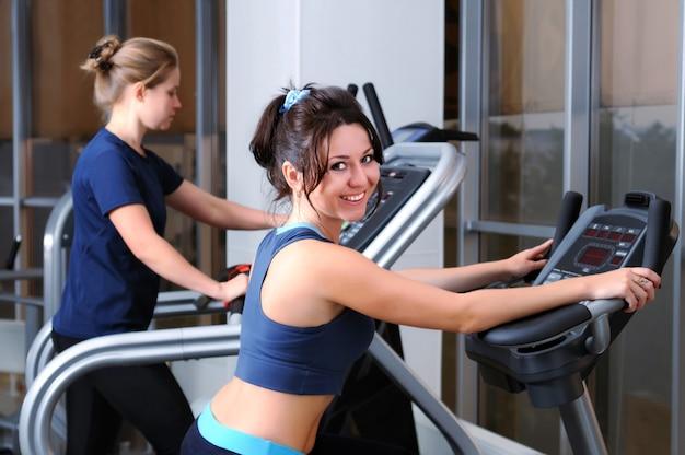 Mulher morena branca bonita sorridente posando de treinamento na bicicleta ergométrica.
