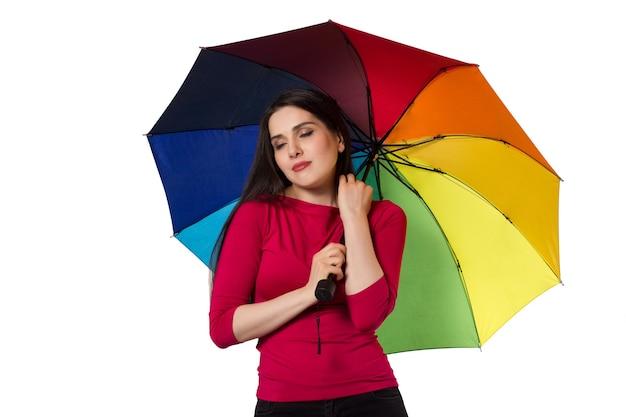 Mulher morena branca sob o guarda-chuva colorido do arco-íris em fundo branco