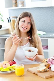Mulher morena brilhante que come cereais com raspberrie na cozinha