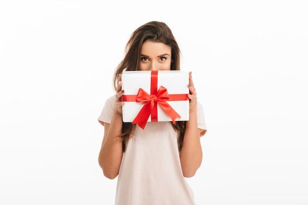 Mulher morena brincalhão em t-shirt se escondendo atrás de caixa de presente sobre parede branca