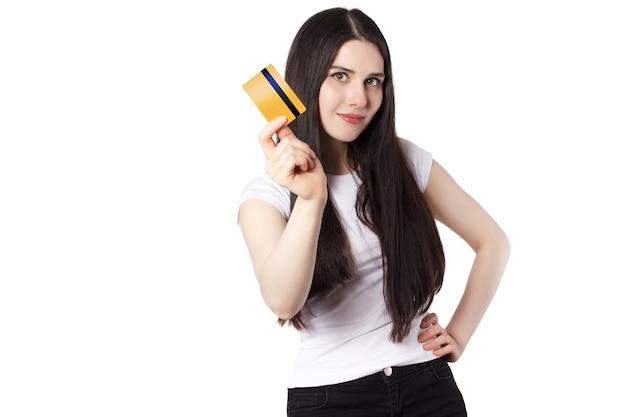 Mulher morena brincalhona em uma camiseta branca demonstrando seu cartão de crédito do banco ouro para simulação