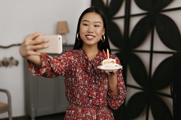 Mulher morena bronzeada com vestido floral vermelho segura o telefone e tira uma selfie com pedaços saborosos de bolo de aniversário