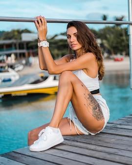 Mulher morena bronzeada e tatuada em forma de short jeans azul claro e blusa branca sentada no cais de madeira à luz do sol