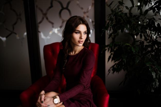 Mulher morena brunet elegante sexy no sofá de couro