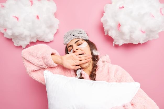 Mulher morena cansada de olhos fechados cobre a boca com a mão usando máscara de dormir e pijama
