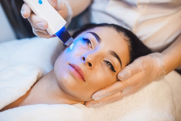 Mulher morena caucasiana deitada em um spa durante procedimentos de tratamento facial com tecnologias modernas