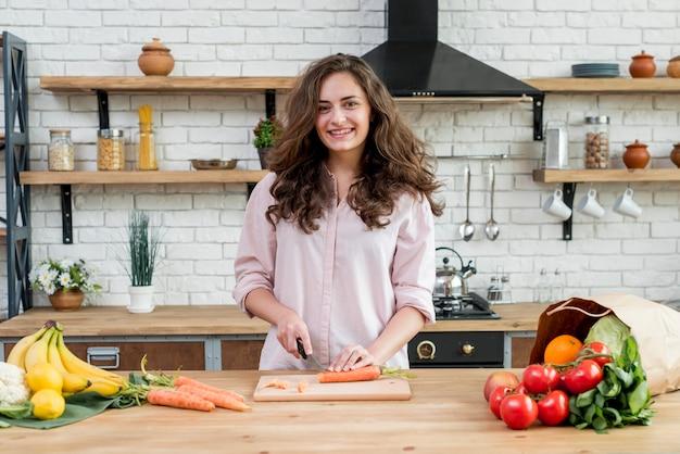 Mulher morena, cenouras cortantes
