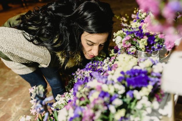 Mulher morena cheirando flores em um mercado à noite.