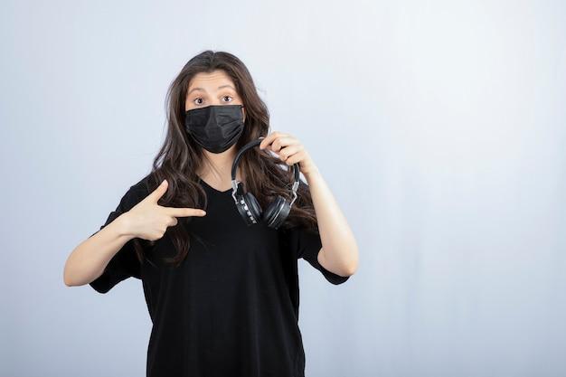 Mulher morena com cabelo comprido em máscara médica apontando para fones de ouvido.