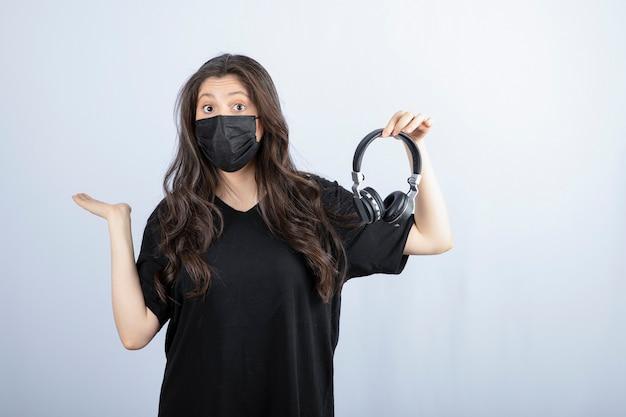 Mulher morena com cabelo comprido em máscara médica segurando fones de ouvido.