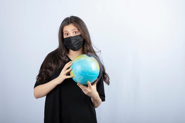 Mulher morena com cabelo comprido em máscara médica segurando o globo do mundo.