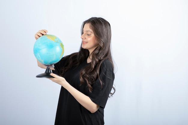 Mulher morena com cabelo comprido escolhe um lugar para viajar no mundo.