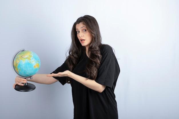Mulher morena com cabelo comprido, segurando o globo do mundo e posando.