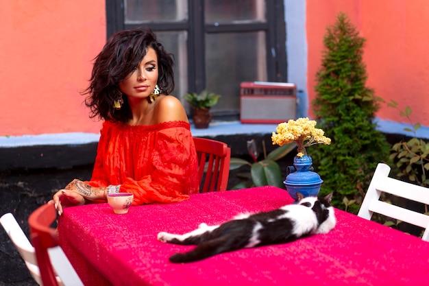 Mulher morena com cabelos cacheados e ombros nus, tomando um café enquanto olha para o gatinho