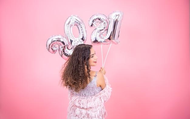 Mulher morena com cabelos cacheados em roupas festivas na parte de trás, posando em uma parede rosa com balões prateados para o ano novo em suas mãos