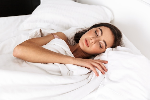 Mulher morena com cabelos escuros sorrindo, enquanto deitada e dormindo na cama em linho branco