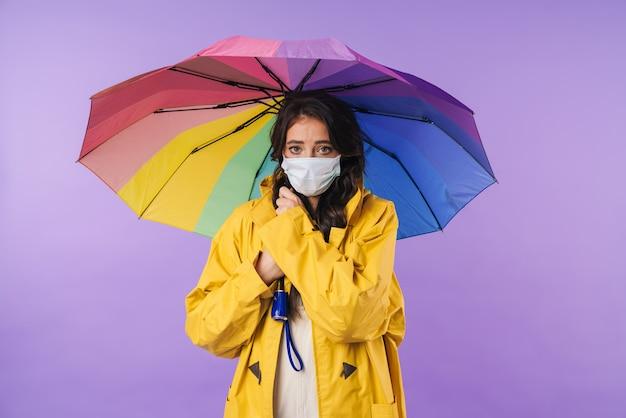 Mulher morena com capa de chuva amarela posando isolado sobre a parede roxa, segurando guarda-chuva usando máscara médica.