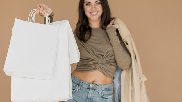 Mulher morena com casaco no ombro e sacolas de compras