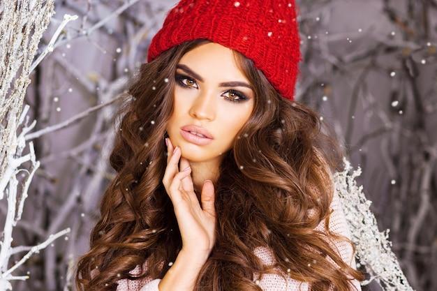 Mulher morena com copo vermelho entre árvores nevadas