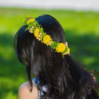 Mulher morena com coroa de flores amarelas na cabeça.