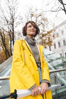 Mulher morena com corte de cabelo bob usando óculos e capa de chuva amarela, explorando marcos em lugar turístico