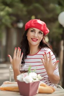 Mulher morena com lábios vermelhos em um boné vermelho e camiseta listrada, sentado no café ao ar livre