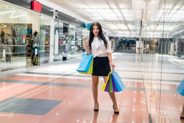 Mulher morena com leque de dólar fazendo compras