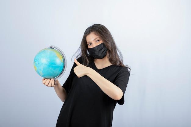 Mulher morena com máscara médica com o globo terrestre aparecendo o polegar