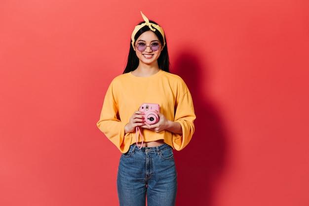 Mulher morena com óculos lilás sorrindo e tirando fotos na frente rosa