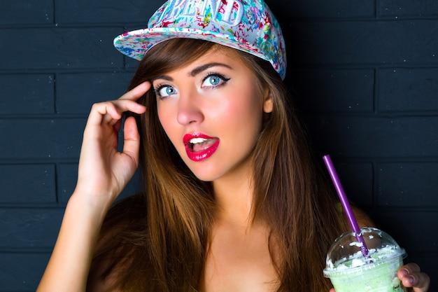 Mulher morena com olhos azuis incríveis, maquiagem brilhante, sorriso bonito, camiseta estampada, segurando batido saboroso, parede urbana.