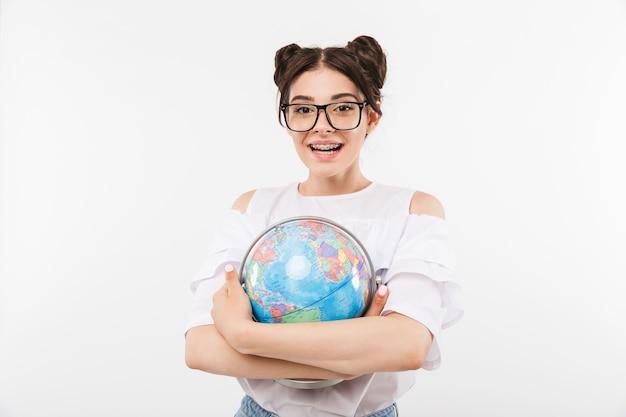 Mulher morena com penteado de pã duplo e aparelho dentário usando óculos, sorrindo enquanto segura o globo terrestre, isolado no branco