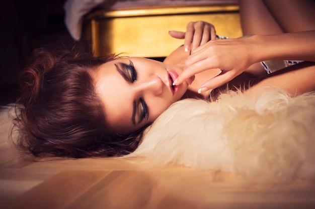 Mulher morena com penteado encaracolado, deitado no chão perto da cama de luxo