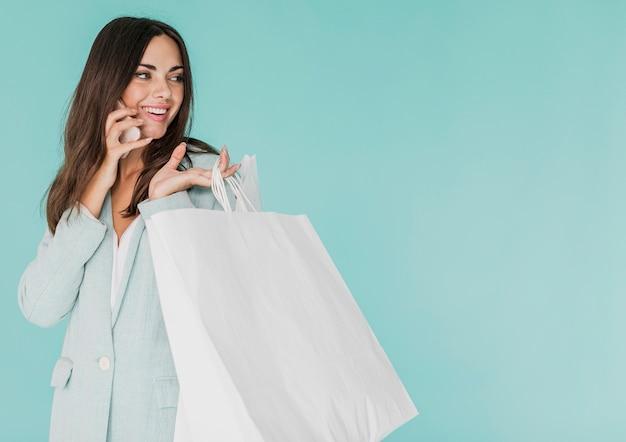 Mulher morena com sacos de compras, falando ao telefone