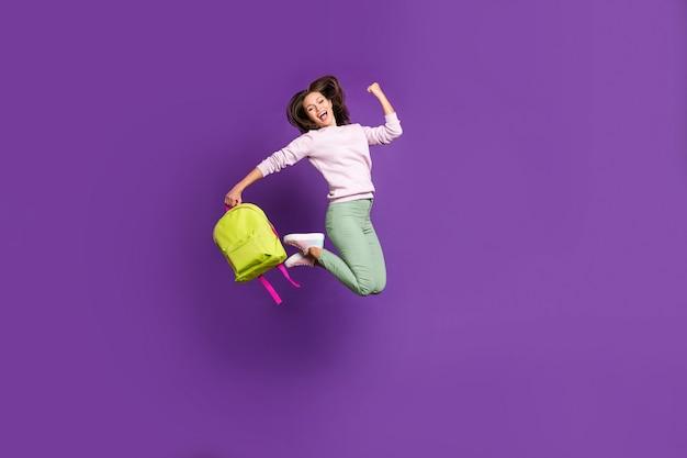 Mulher morena com suéter pastel posando contra a parede roxa