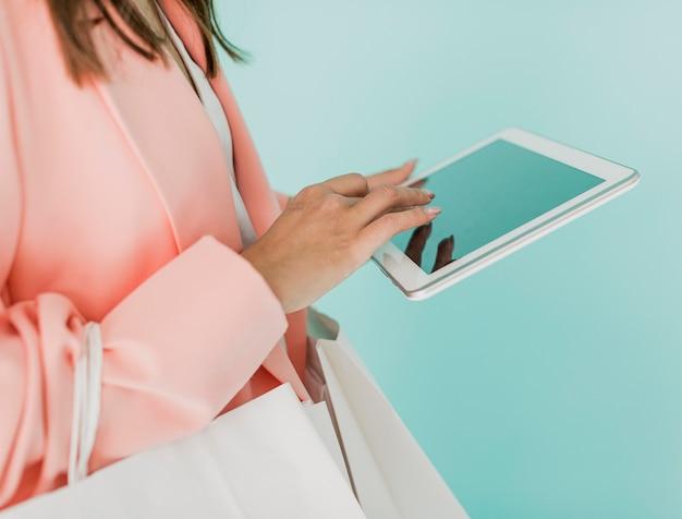 Mulher morena com tablet e sacolas de compras