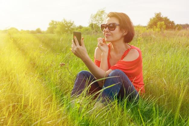 Mulher morena com telefone na grama