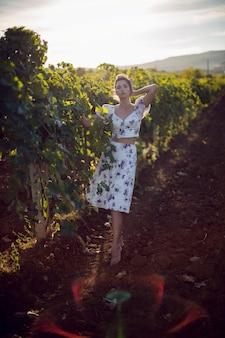 Mulher morena com um vestido branco em um vinhedo no verão na itália