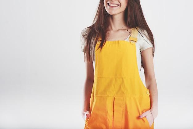 Mulher morena com uniforme amarelo encostada na parede branca do estúdio