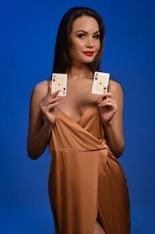 Mulher morena com vestido de seda dourado, sorrindo, mostrando duas cartas de jogar posando na parede azul
